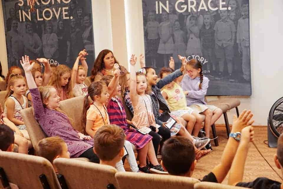 vacation bible school picture of kids laughing inside the church sanctuary